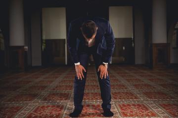 Young Muslim man praying in a mosque.