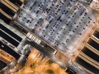 Transportation, cars on big parking at night. Aerial view in Krakow, Poland. Railway station and autobus station