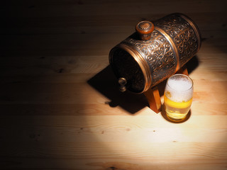 Barrel and glass of light beer on a wooden background