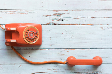 Retro orange-red telephone on the old wooden table with copy space for text or your subject in the past.