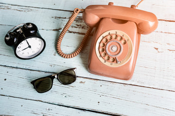 Retro orange-red telephone and the sunglasses on the old wooden table waiting for summer travel.