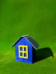 blue model of house as symbol on green background
