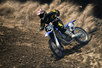 Motocross rider creates a large cloud of dust and debris