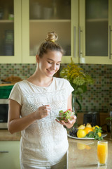 Portrait of an attractive woman with a bowl of fresh salad in the kitchen. Concept photo, vertical