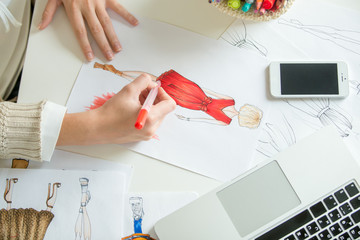Hands colouring a clothing design sketch in red. Concept photo, top view, closeup, close-up