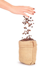coffee beans falling from the hand into the bag