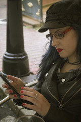 leather young woman with mobile phone in a cafe