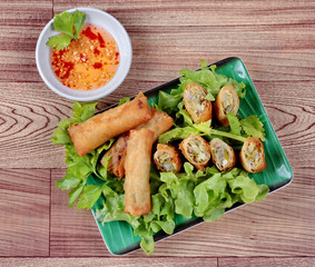 "Deep fried spring roll  as four sheet wrap  fried vermicelli and sliced cabbage in roll bar to deep fried call ""Por Peai J and sour sweet sauce."