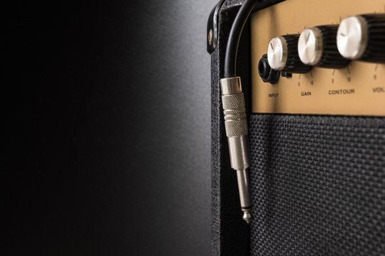 Black guitar amplifier with jack cable on black background