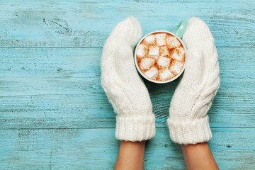 Woman hands in mittens hold cup of hot cocoa or chocolate with marshmallow on turquoise vintage table from above. Flat lay style.