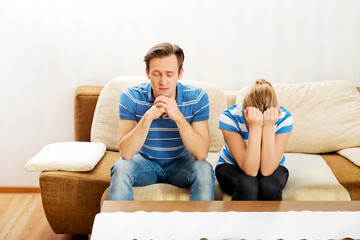 Worried couple after fight sitting on sofa