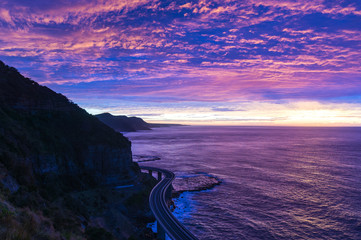 Sea Cliff Bridge on sunrise with beautiful pink and purple, violet sky and ocean shore on the background. The Bridge is part of  Grand Pacific highway and is scenic route along coastal NSW, Australia