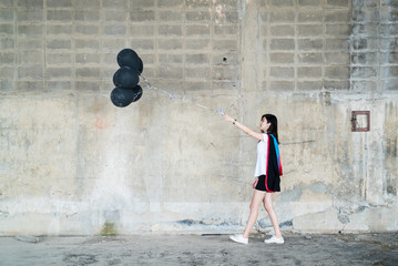 Portrait of graduate girl with black balloon inside a godown