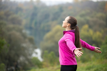 Portrait of an attractive woman outdoors in a sporstwear, her hands outstretched. Concept photo, side view