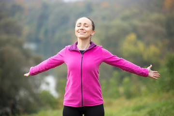Portrait of a smiling young woman outdoors in a sportswear, her hands outstretched, eyes closed. Concept photo