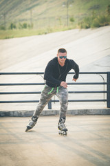 young man with inline skates ride in summer park seafr