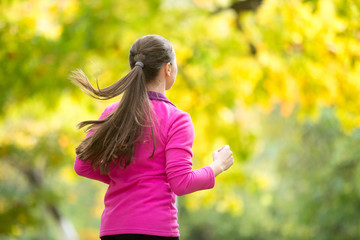 Profile portrait of a young attractive smiling woman jogging away in the autumn. Concept photo, rear view