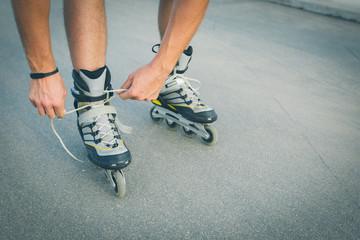 Man preparing for roller skating, putting on rollerskates