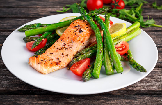 Fried salmon with asparagus, tomatoes, lemon, yellow lime on white plate