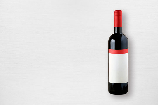 Red wine bottle on white table top view