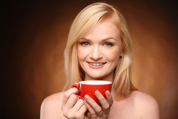 Beautiful girl with cup of coffee on dark background