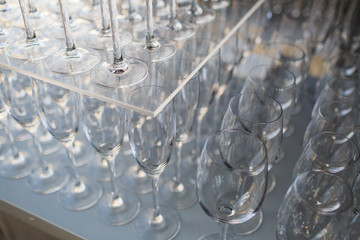 Sparkling wingeglasses stand under the glass tray with champagne