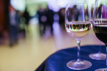 A look throught the glass with white wine on a hall full of gues