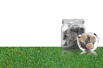 coins in a glass jar on grass floor ,savings coins - Investment And Interest Concept saving money concept, growing money on piggy bank. isolated on white background