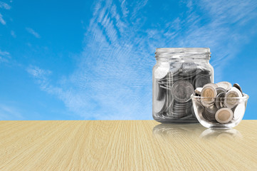 coins in a glass jar on Wood floor ,savings coins - Investment And Interest Concept saving money concept, growing money on piggy bank. isolated on blue sky background