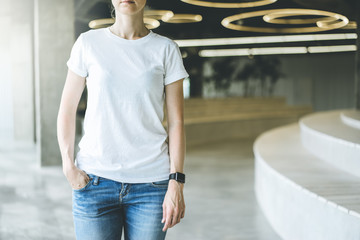 Girl in white T-shirt and blue jeans standing indoor with her hand in her pocket.On second hand digital gadget smartwatc.Nearby places for sitting with wooden texture. Mock up.