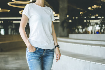Girl in a white T-shirt and blue jeans standing in a room with a modern interior with one hand in his pocket, on hand of girl digital gadget - smartwatch.Blurred background. Mock up.
