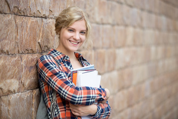 Portrait of a smiling attractive student with books against the brick wall. Back to school concept photo