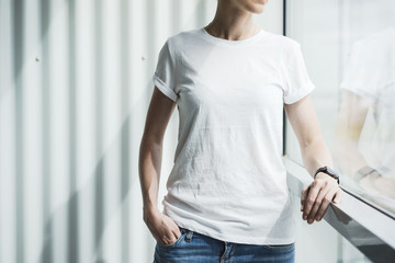 Closeup of a female torso. A woman in a white T-shirt and blue jeans standing in the room leaning on the window frame. In the background a white wall. In a femal's hand smartwatch. Mock up.