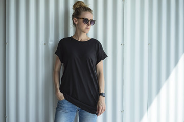 Girl in sunglasses, a black T-shirt and blue jeans standing with her hand in her pocket in a room against a white wall. On hand of the young woman digital gadget - smartwatch. Mock up.