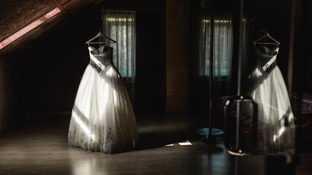 Wedding dress hanging on a hanger in the dark