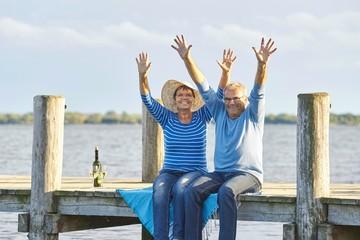 Senioren beim Picknick mit Wein am See, Lebensfreude
