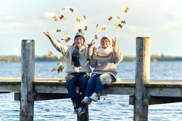 buntes Herbstlaub werfen, Senioren am Steg