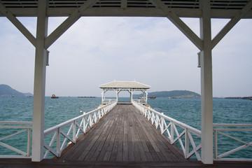 Wooden white bridge into the sea