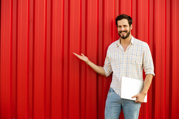 man presenting one side with laptop in hands on red background