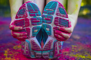 Female hand holding her shoes covered dry paint