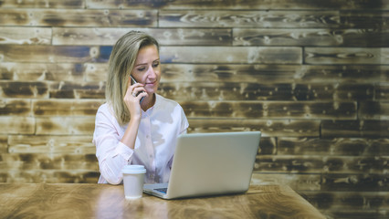 Young business woman sitting at a table,talking on smartphone and shopping online,on table laptop and cup of coffee.Blonde girl sitting at the table against the background of wooden wall Shou Sugi Ban
