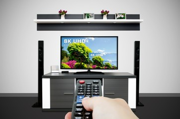 Watching television in modern TV room. Compare of television resolution
