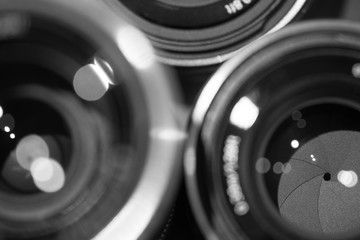closeup macro of camera lenses with reflections low key black and white image with aperture blades