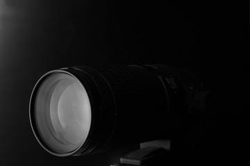 closeup macro of camera lens with reflections low key black and white image