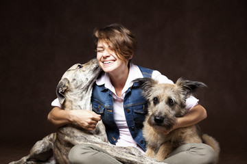 Beautiful young woman with two funny dogs on a dark background.