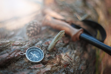 Magnetic compass on a wooden table. Nearby lies the binoculars