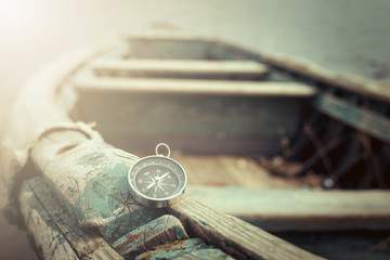 Travel concept, compass, sand and rope on wooden background