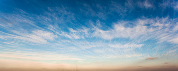 Blue sky with feather shaped cloud and sunset orange color bottom.