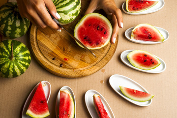 Slices of watermelon. Children's hands cooking fruit salad. Top view