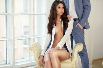 Beautiful lady in shirt with handsome guy in suit. Young couple is hugging each other. Portrait of girl in underwear and boy indoors in passionate pose. Beauty woman with attractive lace lingerie